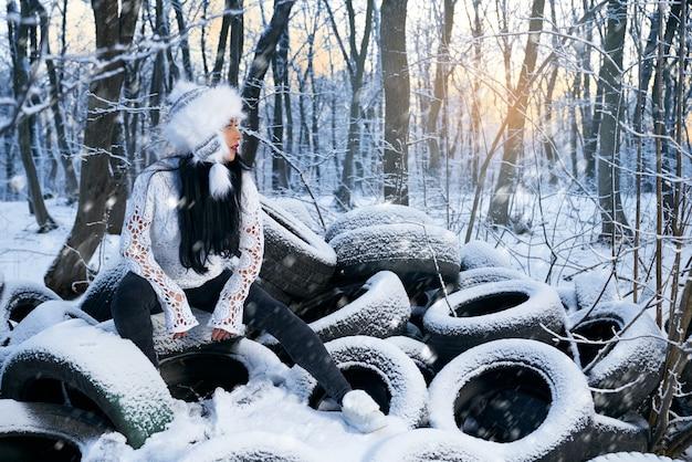 Fille au chapeau assis sur des pneus de voiture en forêt en hiver.