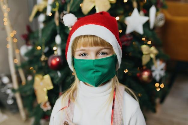 Fille au chapeau et au masque du père noël, période de noël, verrouillage en vacances, covid-19, coronavirus.