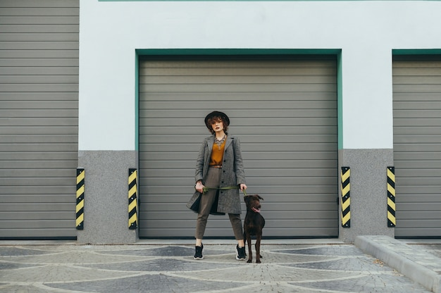 Fille au chapeau et aux cheveux bouclés tient une laisse avec un chien à la main et pose à la caméra
