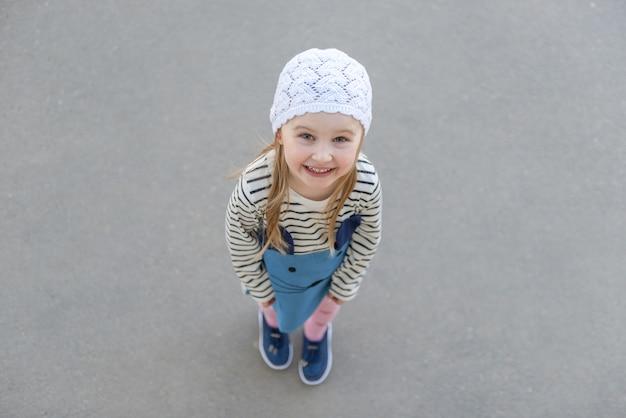 Fille au chapeau blanc, debout à l'extérieur, souriant