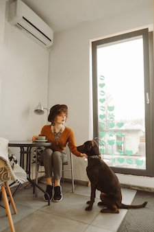 Fille au chapeau boit du café et joue avec un chien dans un café léger et confortable
