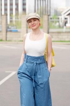 Fille au chapeau carré, pantalon blanc t shrt et large bleu marchant au parking