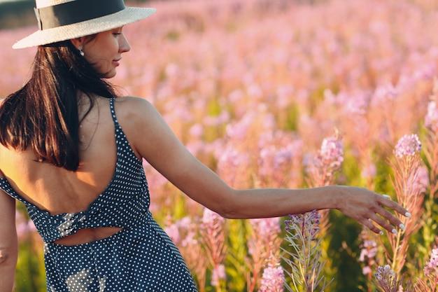 Fille au chapeau sur le champ de fleurs sally en fleurs. fleurs et femme lilas.