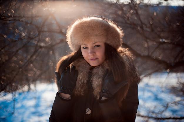 Fille au chapeau chaud avec des oreillettes sur le fond de la neige