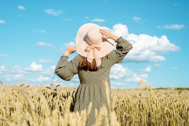 Fille au chapeau dans un champ avec des épis de maïs sur le dos, récolte d'été de pain. concept de liberté.