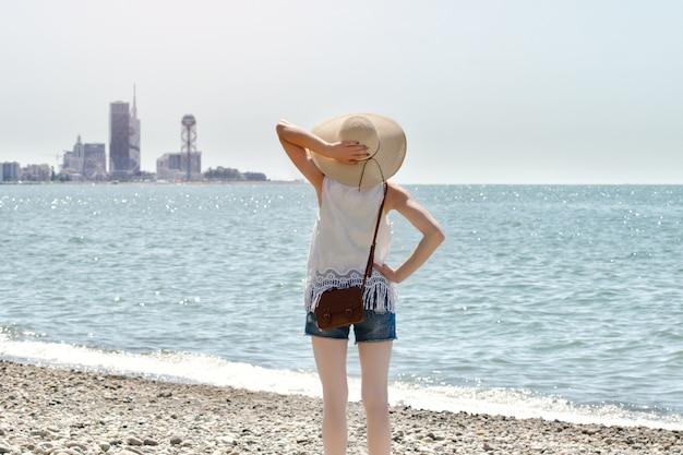 Fille au chapeau debout au bord de la mer