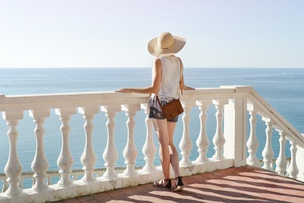 Fille au chapeau debout sur les escaliers et regardant la mer. vue arrière