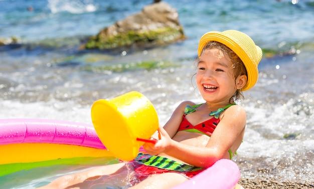 Fille au chapeau de paille jaune joue avec le vent, l'eau et un distributeur d'eau dans une piscine gonflable sur la plage.