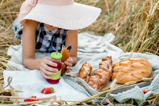 Fille au chapeau de paille sur pique-nique vue de dessus. pique-nique esthétique en plein air avec du pain et des fruits, des baies et des croissants.