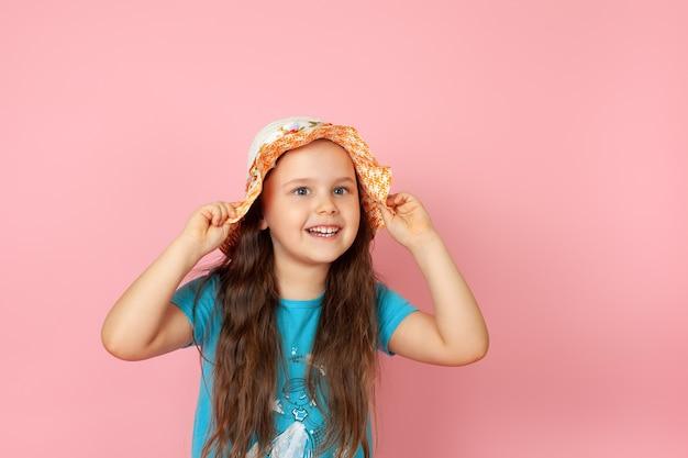 Fille au chapeau de paille et robe bleue avec ses mains tenant le bord de son chapeau