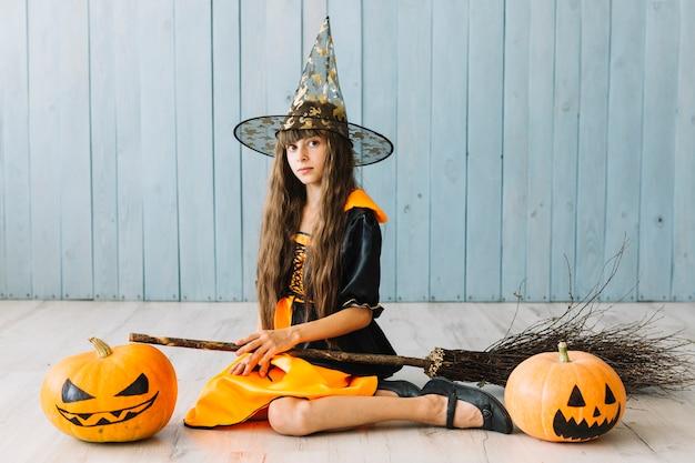 Fille au chapeau pointu assis sur le sol avec des citrouilles