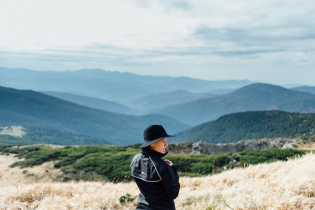 Fille au chapeau posant dans le contexte de la chaîne de montagnes.