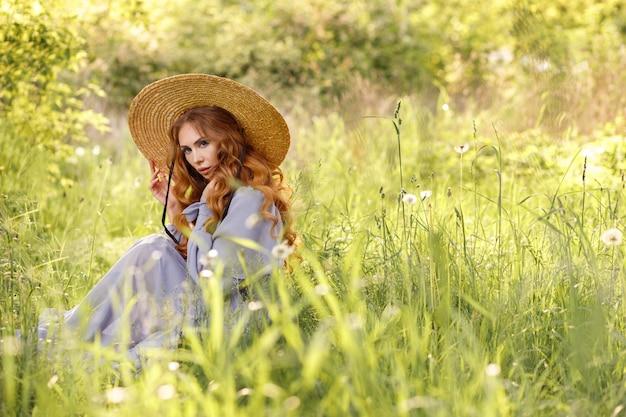La fille au chapeau et à la robe est assise dans l'herbe verte du jardin en été. poutres de sonza