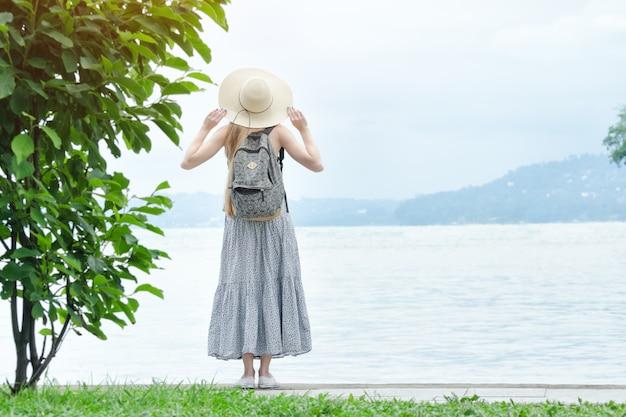 Fille au chapeau avec un sac à dos se tenant sur une jetée à la mer