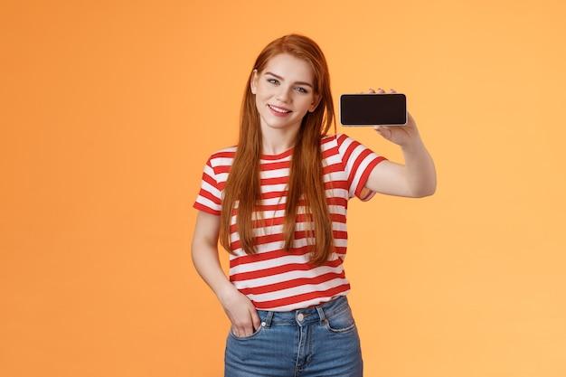Une fille au gingembre caucasienne séduisante et confiante présente une application pour smartphone recommande un jeu télévisé cool ...