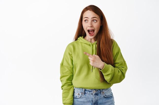 Une fille au gingembre étonnée et heureuse laisse tomber la mâchoire excitée, pointant et regardant vers la gauche avec admiration debout sur blanc