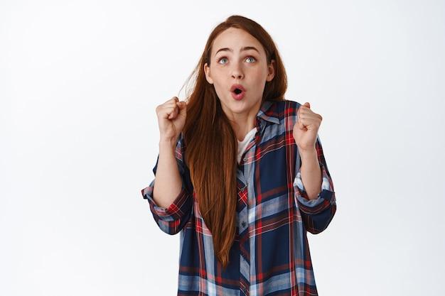 Une fille au gingembre excitée dit wow, dansant d'excitation, regardant l'écran de télévision et chantant, regardant un match de sport et s'enracinant pour l'équipe, debout sur du blanc.