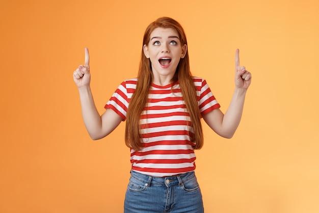 Une fille au gingembre gaie et excitée voit une opportunité incroyable pointer vers le haut un halètement amusé de la mâchoire tombante ...