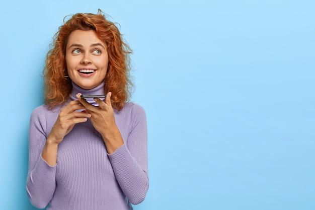 Une fille au gingembre heureuse fait un appel vocal, tient le smartphone près de la bouche, heureuse d'avoir une bonne conversation avec un ami, sourit joyeusement, porte un pull violet, se tient contre le mur bleu, copiez l'espace de côté pour le texte