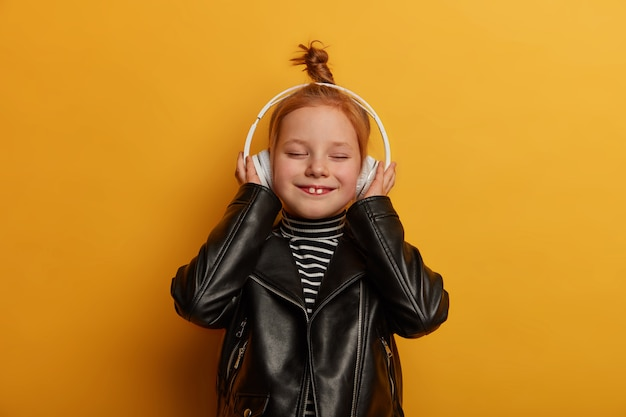 Une fille au gingembre heureuse montre deux dents, écoute de la musique dans des écouteurs, vêtue d'une veste en cuir, ferme les yeux avec plaisir, passe du temps libre seule, isolée sur un mur jaune. enfants, animations