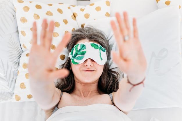 Fille au lit s'est réveillée, sommeil, matin, procédures du matin, petit-déjeuner, oreiller, masque de sommeil, mains