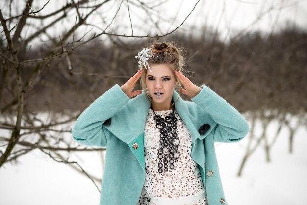 Fille Au Manteau Bleu Dans La Forêt Enneigée Tient Sa Tête à Deux Mains Photo Premium