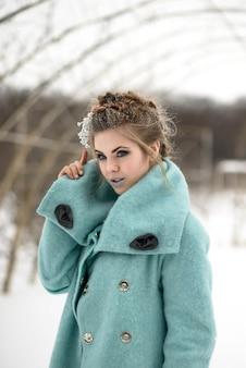 Fille au manteau bleu en hiver forêt enneigée main tenant le collier