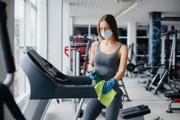 La fille au masque désinfectant le matériel de gym pendant une pandémie.