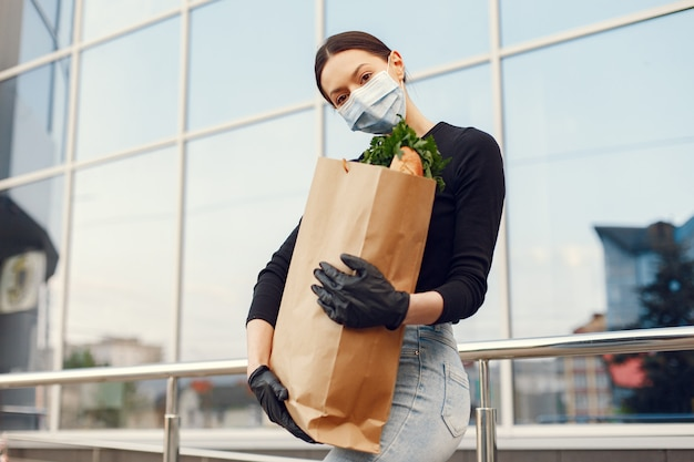 Fille au masque de protection détient le paquet de produits