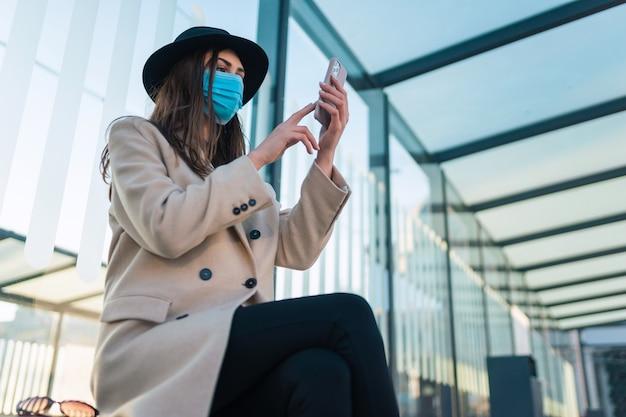 Fille au masque de protection avec téléphone