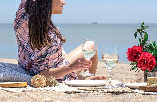 Fille au repos sur un pique-nique avec un verre dans ses mains avec vue sur la mer. concept de vacances d'été.