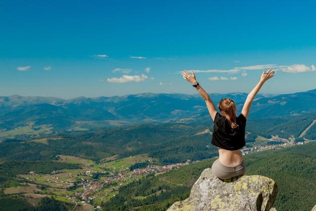 La fille au sommet de la montagne leva les mains.