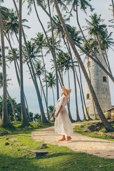 Fille au sri lanka sur une île avec un phare.