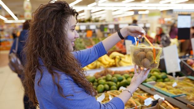 Une fille au supermarché choisit le kiwi