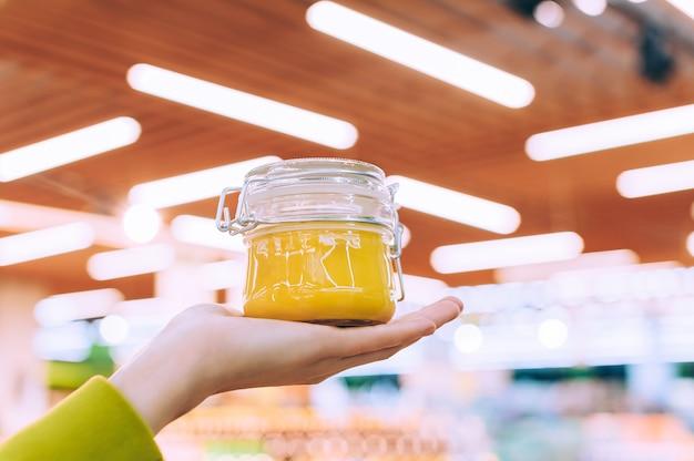 La fille au supermarché tient un bocal en verre de miel. sur fond de lampes.