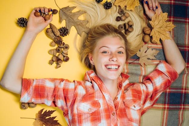 La fille d'automne se prépare pour la vente d'automne. l'humeur d'automne et le temps sont chauds et ensoleillés et la pluie est possible. chute des feuilles. belle blonde sensuelle jouant avec des feuilles.