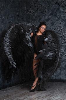 Fille aux ailes d'ange noir dans une pièce sombre.