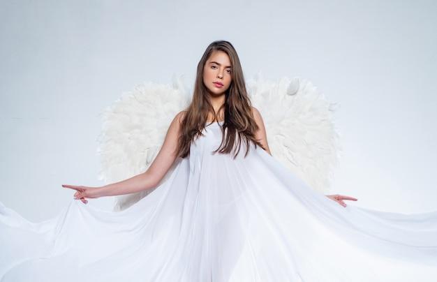 Fille aux ailes d'ange et une robe blanche. femme cupidon