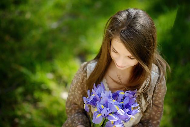 Fille aux beaux cheveux avec un bouquet d'iris violets. vue d'en-haut. flou artistique.
