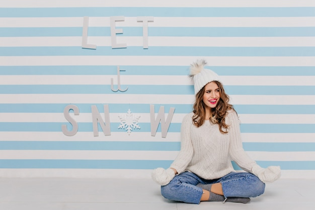 Fille aux boucles méditant sur le sol et en détournant les yeux avec le sourire. portrait en pied dans un mur rayé blanc et bleu