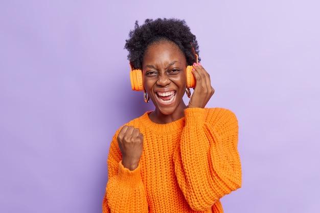 Fille aux cheveux afro serre le poing fait oui geste bénéficie d'un bon son dans les écouteurs modernes écoute la chanson populaire porte un chandail tricoté