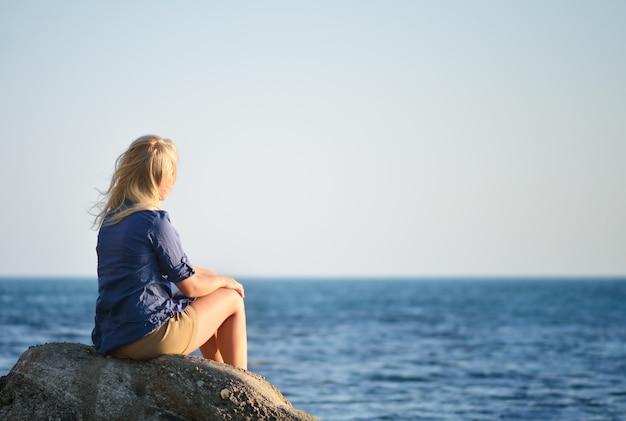 Fille aux cheveux blonds assis sur un rocher et regardant la mer