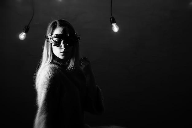Une fille aux cheveux blonds dans un masque noir pose