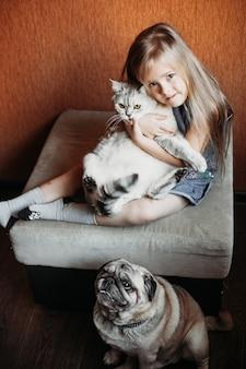 Fille aux cheveux blonds tient un chat