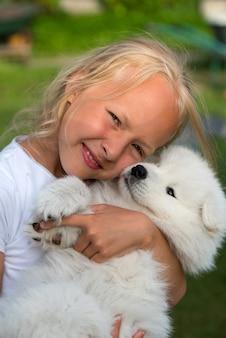 Fille aux cheveux blonds tient dans les mains un petit chiot blanc samoyède