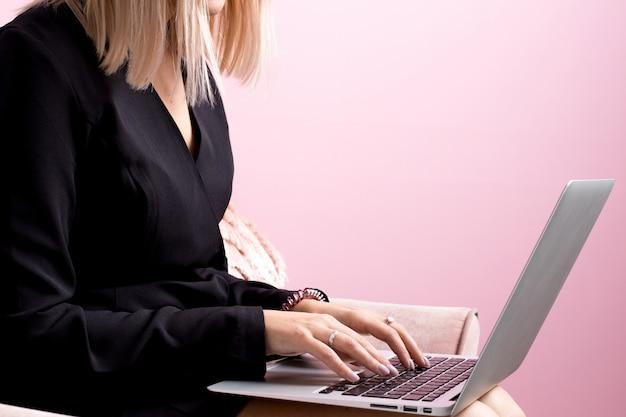 Fille aux cheveux blonds travaille sur un ordinateur portable dans une pièce rose