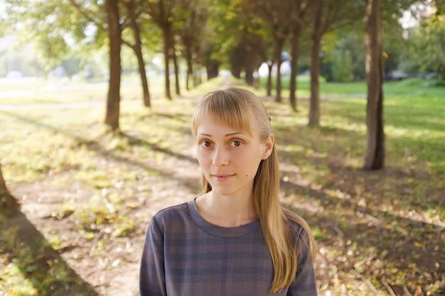 Une fille aux cheveux blonds, vêtue d'une robe rayée, un jour d'été. une jeune femme au regard calme, regardant