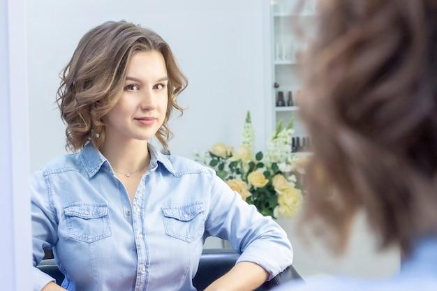 Fille aux cheveux bouclés assis sur une chaise dans un studio de beauté. voir le reflet dans le miroir