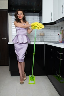Fille aux cheveux bouclés dans une robe de soirée lilas lave le sol de la cuisine avec une vadrouille verte.