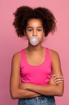 Fille aux cheveux bouclés faisant un bubble-gum